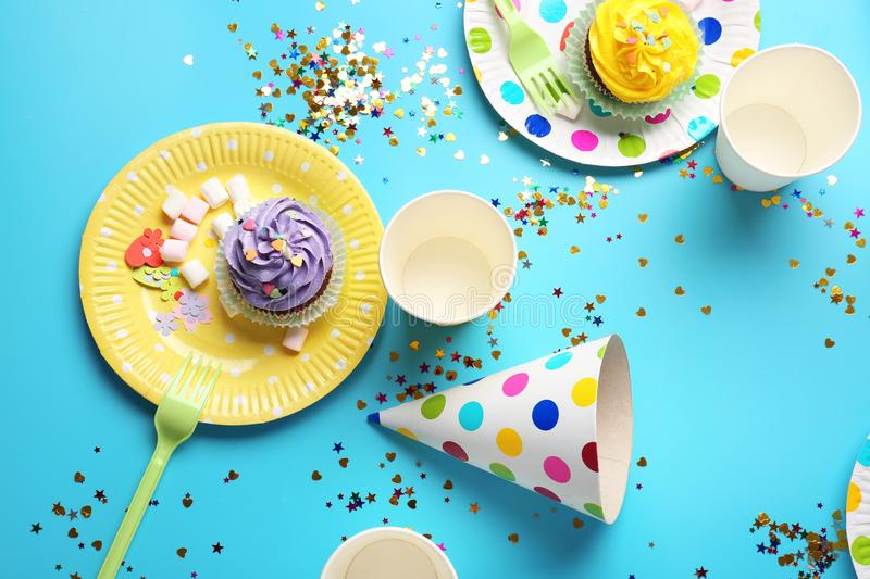 Plates with birthday cupcakes and paper glasses. On table royalty free stock photography