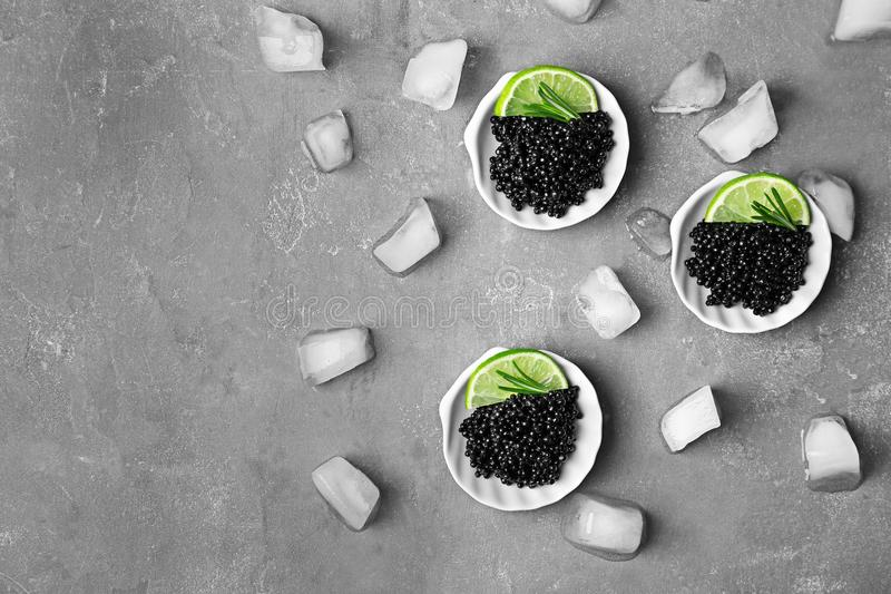 Plates with black caviar and ice cubes stock photo