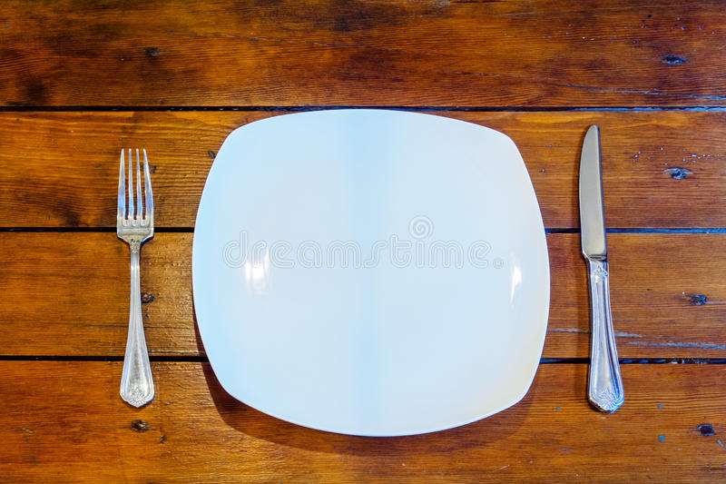 Plates and cutlery on wooden table royalty free stock photos