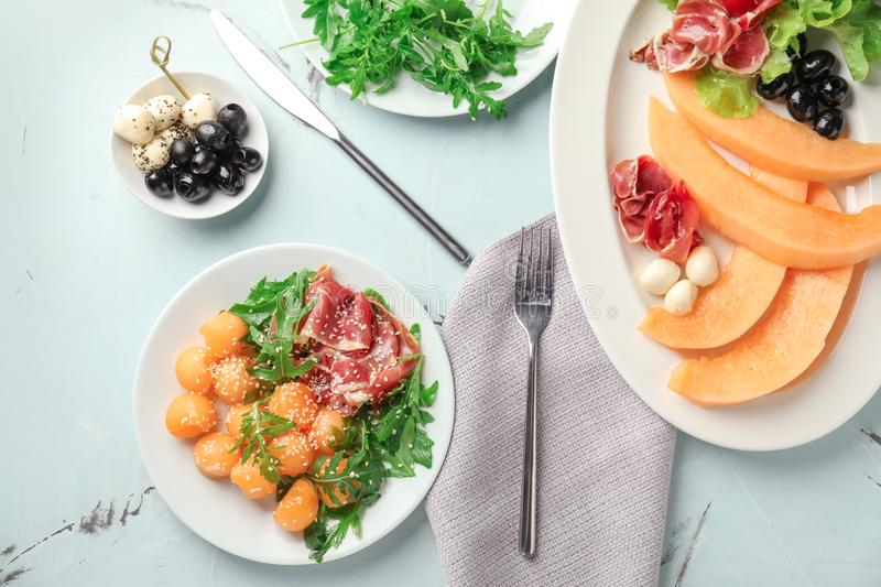 Plates with delicious melon and prosciutto on table, top view stock image