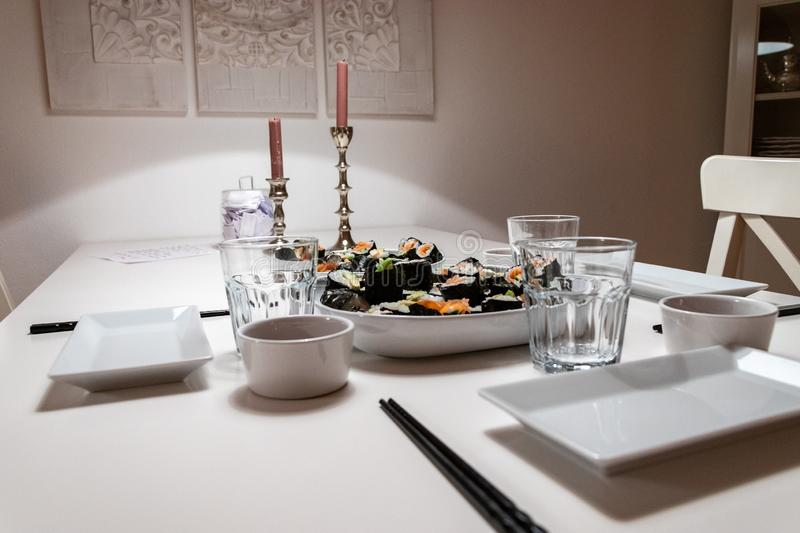 Plates and Dishes on the table in an apartment. self made Sushi roll. Romantic dinner with ambient light from candle. Plates and Dishes on the table in luxury stock photos