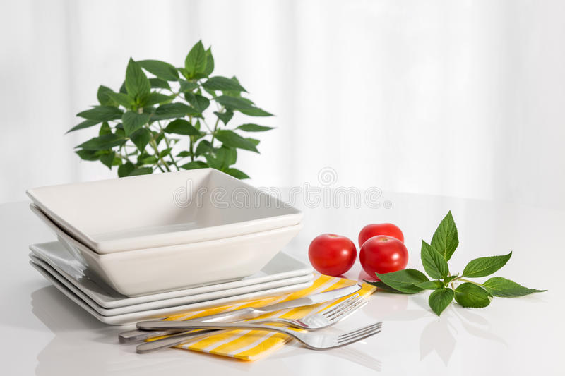 Plates and kitchen utensils on a white table stock image