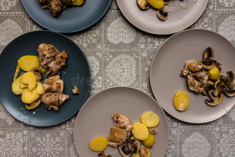 plates of chicken meat with mushroom sauce and potatoes on the table with a gray tablecloth stock images