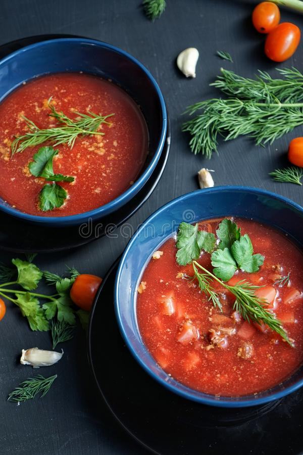 plates with red soup, decorated with fresh herbs, parsley, dill, cherry tomatoes , garlic. stock photo