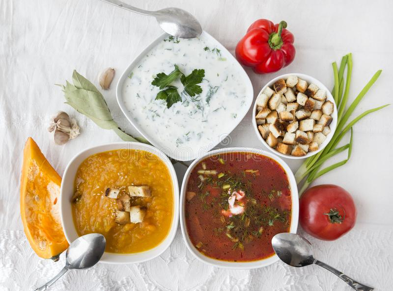 3 plates with soups, top view, borsch, yogurt soup with greens, pumpkin soup, spoons, herbs, vegetables, tomato, pumpkin, pepper,. 3 plates with soups, top view stock photo