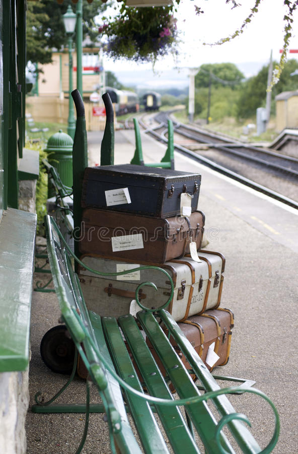 Platform Baggage. A set of period luggage with labels, consisting of old leather cases, set on a trolly on the platform of a retro railway station. Location at stock photos