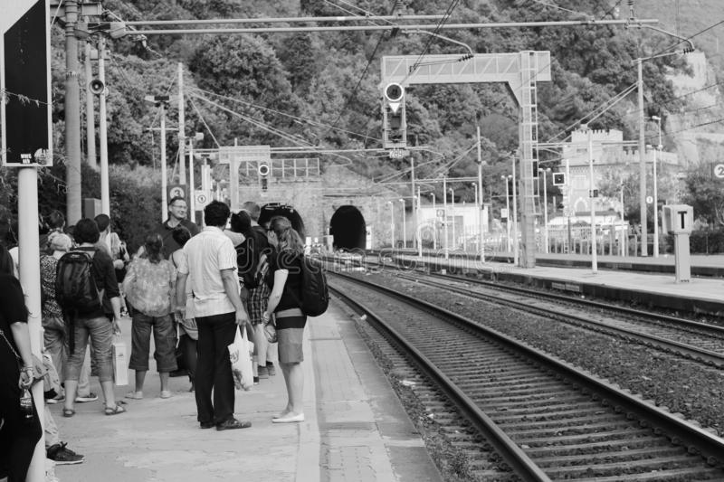 A platform crowded with waiting passengers for the local train service approaches from the tunnel at Monterosso railway station Li royalty free stock images