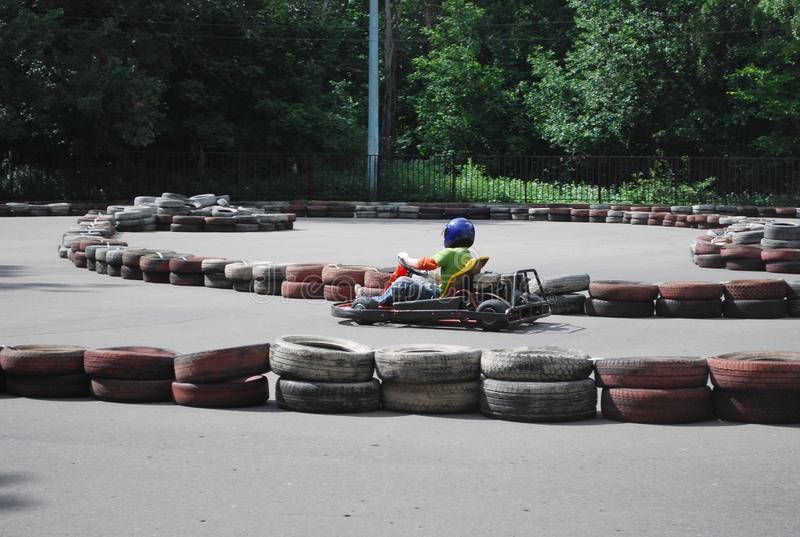 The platform for karting in the Moscow Sokolniki park. Summer sunny day the teenager rides the platform on the racing machine. stock photos