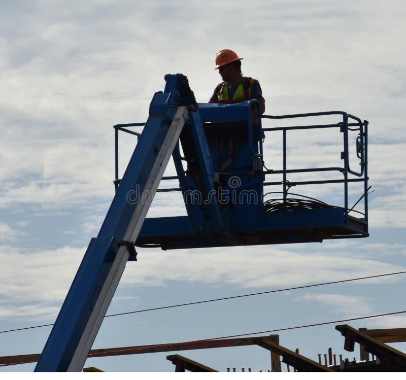 A platform lift raises a worker above a bridge royalty free stock images