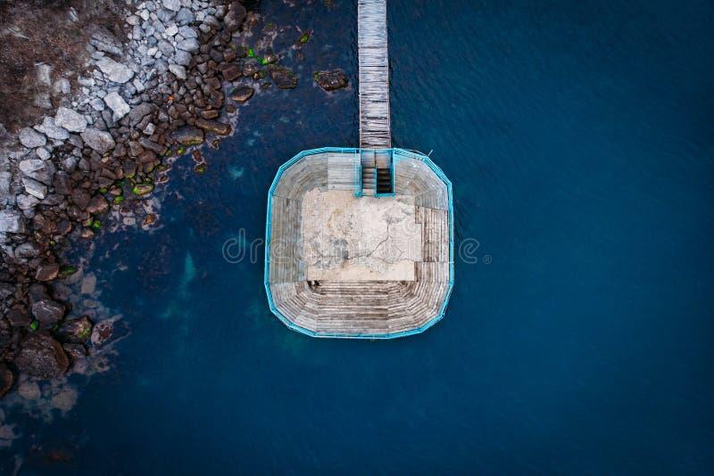 Platforma lub molo z drewnianym mostem blisko dennej skalistej plaży, powietrzny odgórny widok Wakacje i podróż przedmiotów pojęc fotografia royalty free