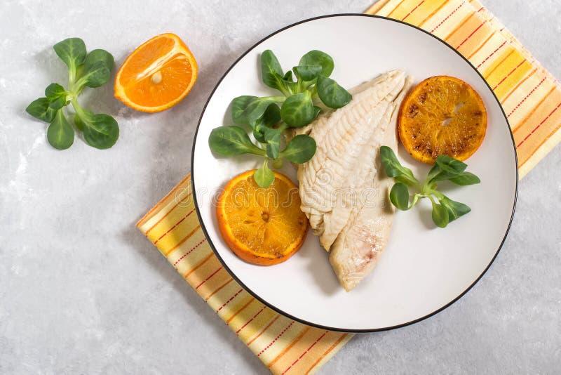 Platija cocida con las mandarinas imagen de archivo