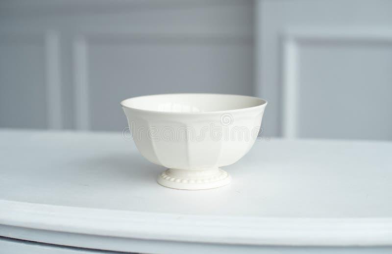 Platillo elegante en la tabla blanca en sitio brillante grande imagen de archivo