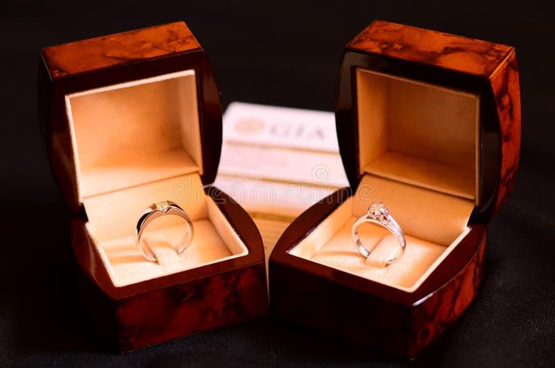 Platin Diamond Ring, Eheringe in einem Kasten auf dunklem Hintergrund lizenzfreies stockbild