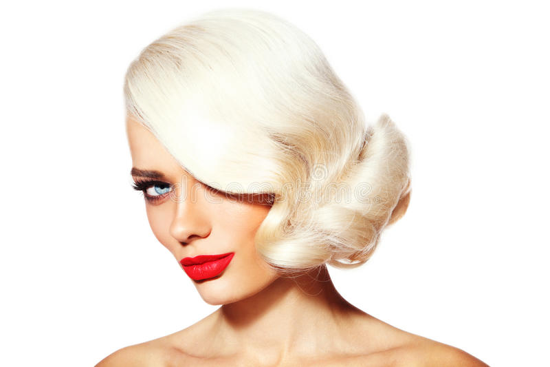 Platinum blonde beauty. Portrait of young beautiful platinum blonde tanned woman with vintage hairdo and red lipstick over white background royalty free stock photos