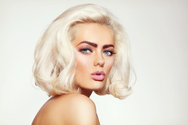 Platinum blonde. Vintage style portrait of young beautiful tanned sensual platinum blonde girl with stylish make-up and hairdo stock photo