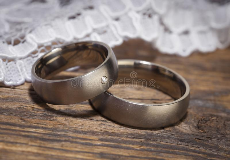 Platinum wedding rings on wooden table stock image