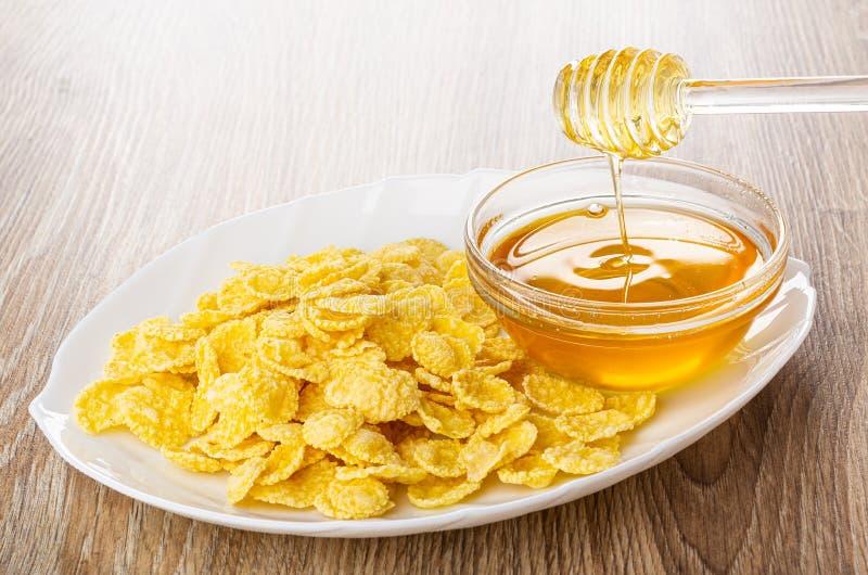 Plato con las avenas, cazo de la miel sobre el cuenco con la miel en la tabla imágenes de archivo libres de regalías