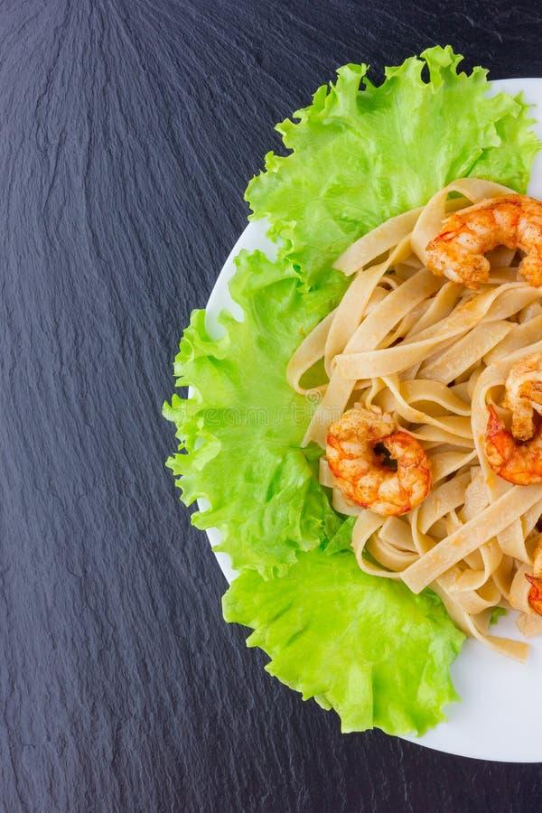 Plato con las pastas y el camarón en la superficie de la pizarra foto de archivo libre de regalías