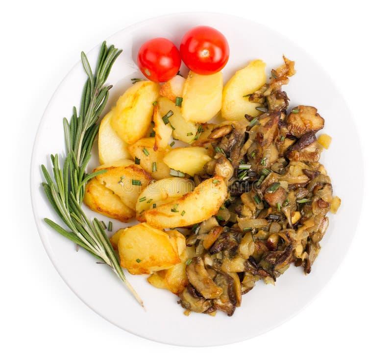 Plato con las patatas fritas y los cepes aislados en un backgroun blanco imagen de archivo libre de regalías