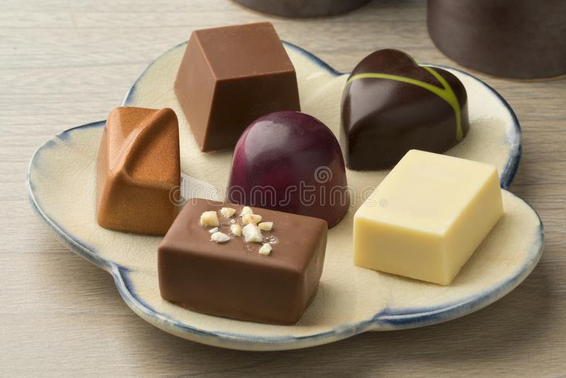 Plato con los caramelos clasificados del chocolate fotos de archivo