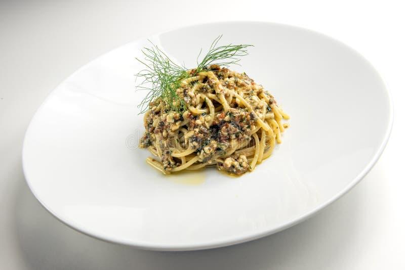 Plato de espaguetis con la salsa de las nueces de pino de las aceitunas de las alcaparras secadas a fotografía de archivo