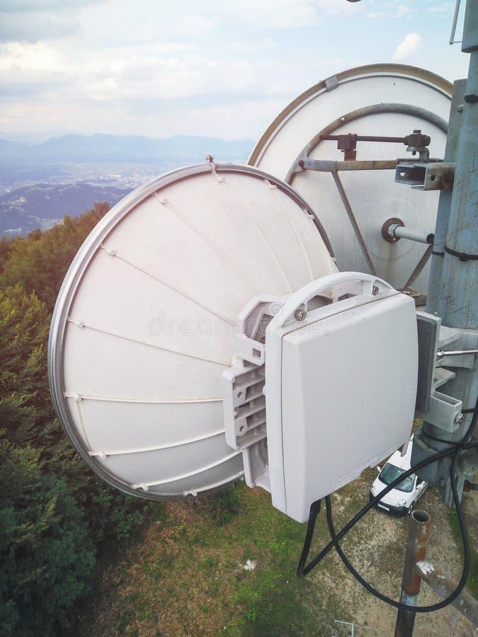 Plato de la antena de la transmisi?n del v?nculo de microonda en una torre celular del metal de la red de la telecomunicaci?n foto de archivo