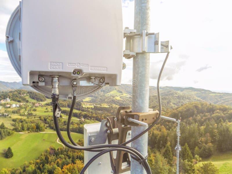 Plato de la antena de la transmisi?n del v?nculo de microonda en una torre celular del metal de la red de la telecomunicaci?n fotografía de archivo