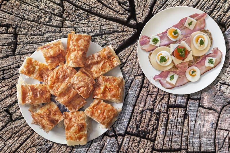 Plato de la empanada arrugada queso de Gibanica del servio queso con la placa del tocino, huevo, jamón y Cherry Tomato Sandwich e imagen de archivo