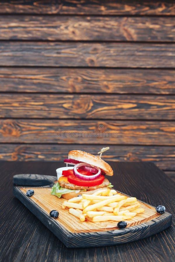 Plato de los alimentos de preparación rápida Hamburguesa con las fritadas en una tabla de cortar de madera Hamburguesa y patatas  imagenes de archivo