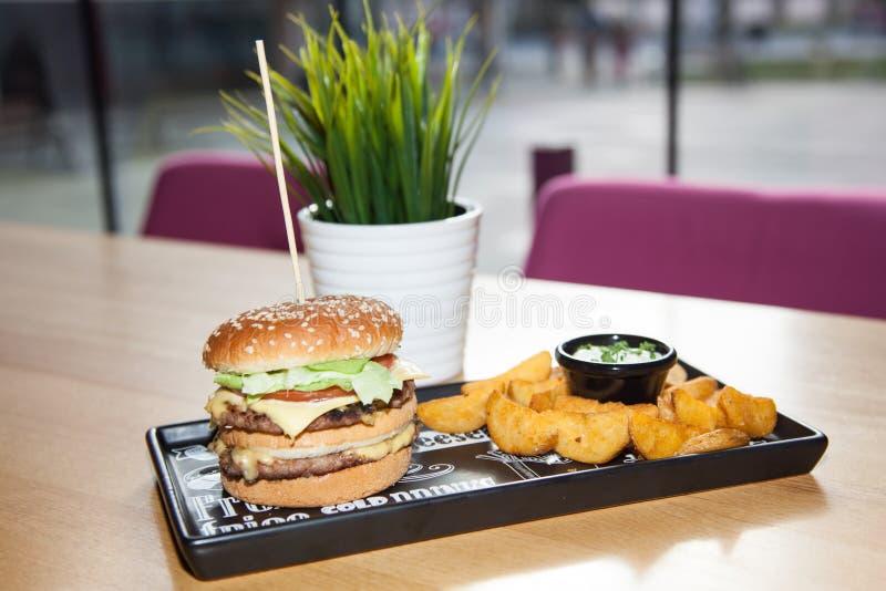 Plato de los alimentos de preparación rápida Patatas del hamburguesa de la carne, fritas y vegeta apetitosos fotografía de archivo