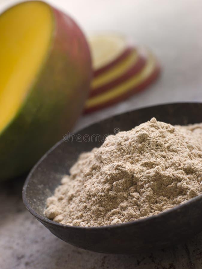 Plato del polvo del mango con el mango fresco rebanado imagen de archivo