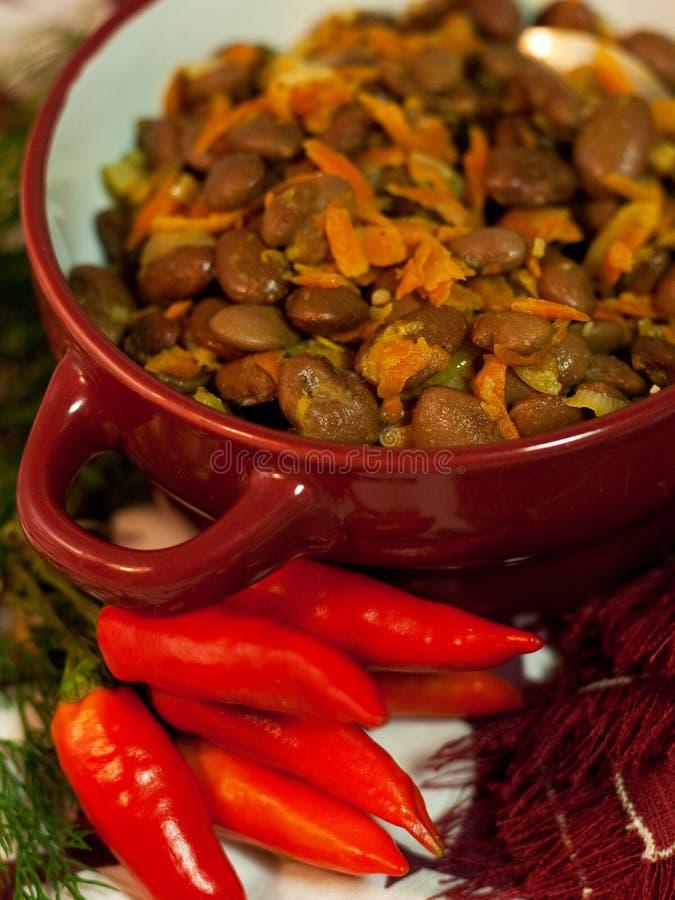 Plato del vegano de habas con las cebollas y las zanahorias fotos de archivo