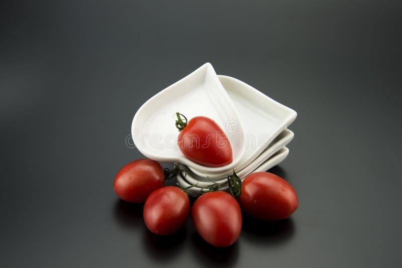 Plato en forma de corazón blanco y pequeños tomates imágenes de archivo libres de regalías