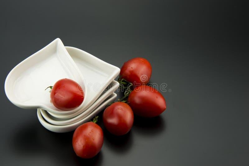 Plato en forma de corazón blanco y pequeños tomates fotos de archivo