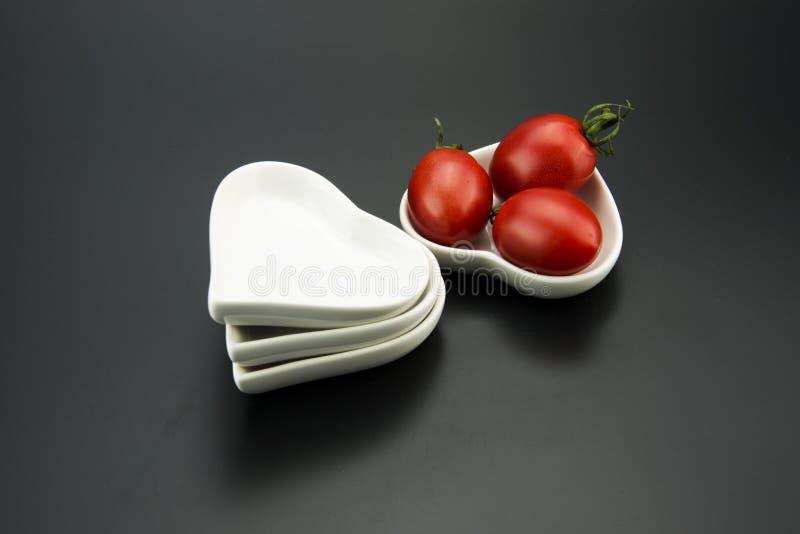 Plato en forma de corazón blanco, y pequeños tomates rojos imágenes de archivo libres de regalías