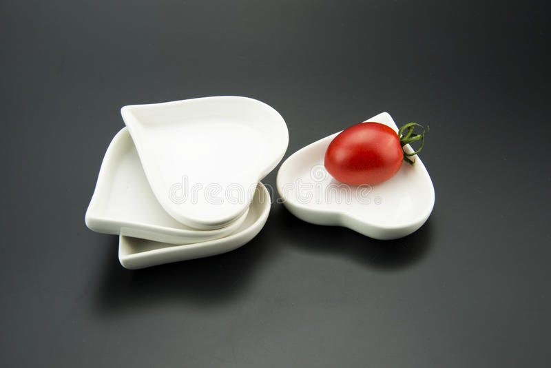 Plato en forma de corazón blanco, y pequeños tomates rojos fotos de archivo