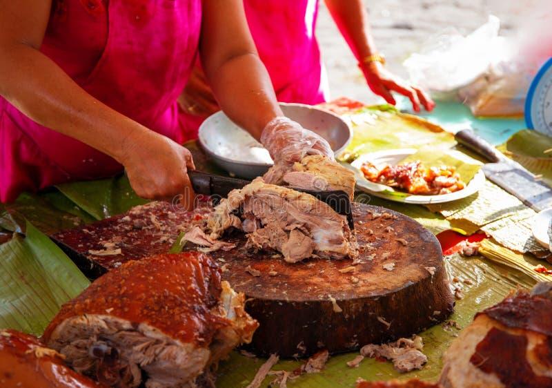 Plato filipino nacional de Lechon con la mano de la camarera La mujer vende el cerdo frito en país asiático imagenes de archivo