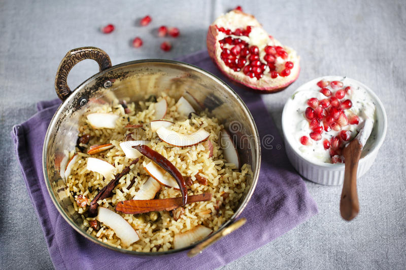 Plato indio del arroz de Biryani con raita del coco y del pommegranate fotos de archivo