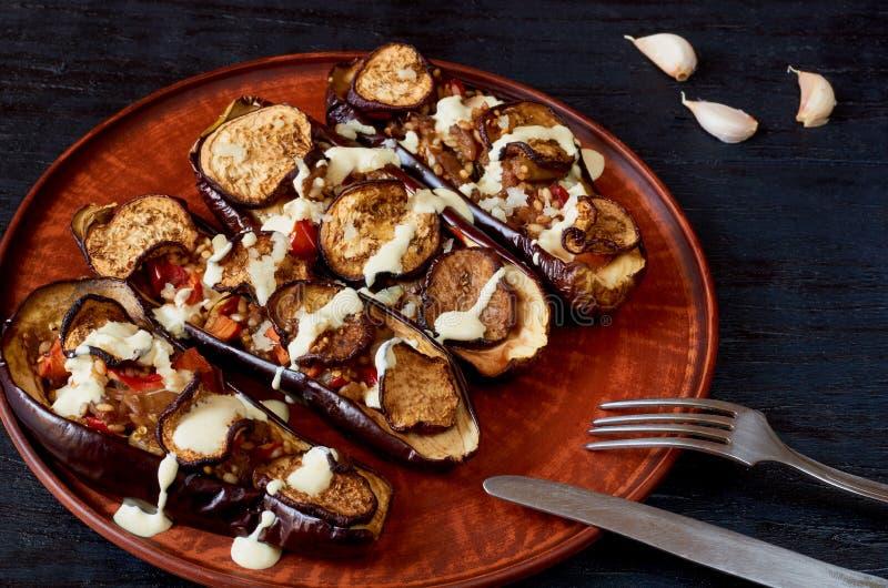 Plato mexicano tradicional - asó a la parrilla las berenjenas rellenas con subida, los tomates, el ajo y la salsa en una placa de foto de archivo