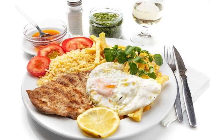 Plato para el almuerzo de la carne frita, chuleta de cerdo con el huevo, patatas Plato portugu?s foto de archivo libre de regalías