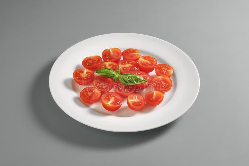 Plato redondo con los tomates de cereza tajados fotografía de archivo libre de regalías