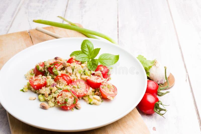 Plato vegetariano de la ensalada de la quinoa en el fondo de madera blanco imágenes de archivo libres de regalías