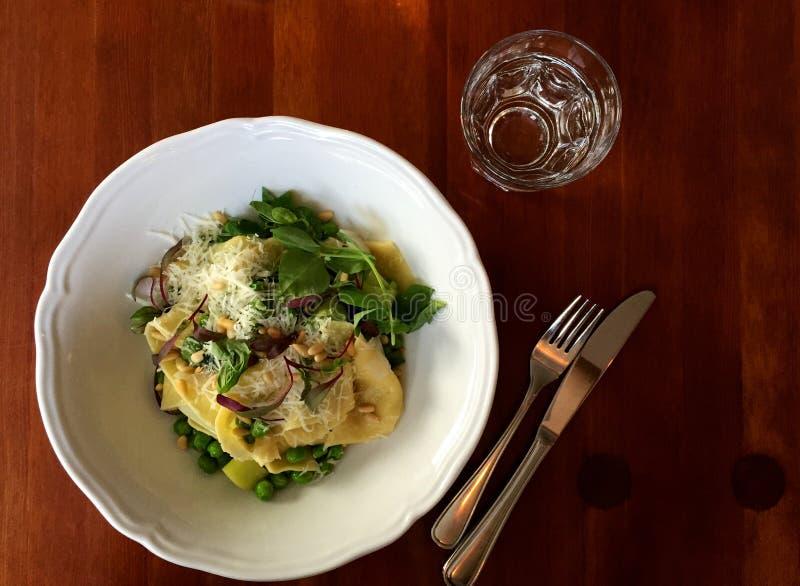 Plato vegetariano de las pastas con los guisantes, los puerros, la albahaca, los microgreens y el queso imagen de archivo libre de regalías