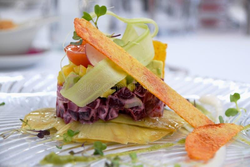 Plato vegetariano del tártaro con remolachas, maíz, el aguacate, los tomates y las verduras de raíz fotografía de archivo