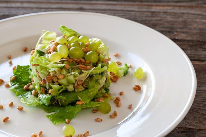 Plato vegetariano: ensalada de la uva con el bróculi, aguacate, pepinos a foto de archivo
