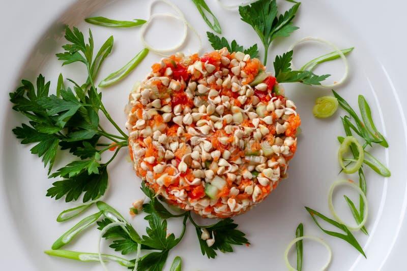 Plato vegetariano: ensalada de las semillas brotadas del alforfón con el pepino foto de archivo