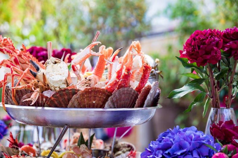 Plato y flores de los mariscos en la tabla del restaurante imagen de archivo