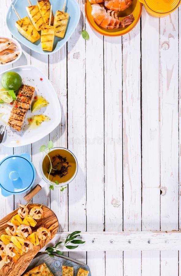 Platos asados a la parrilla de la fruta y de los mariscos en la tabla de madera imagen de archivo