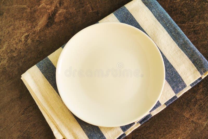 Platos blancos vacíos y manteles a rayas azules foto de archivo