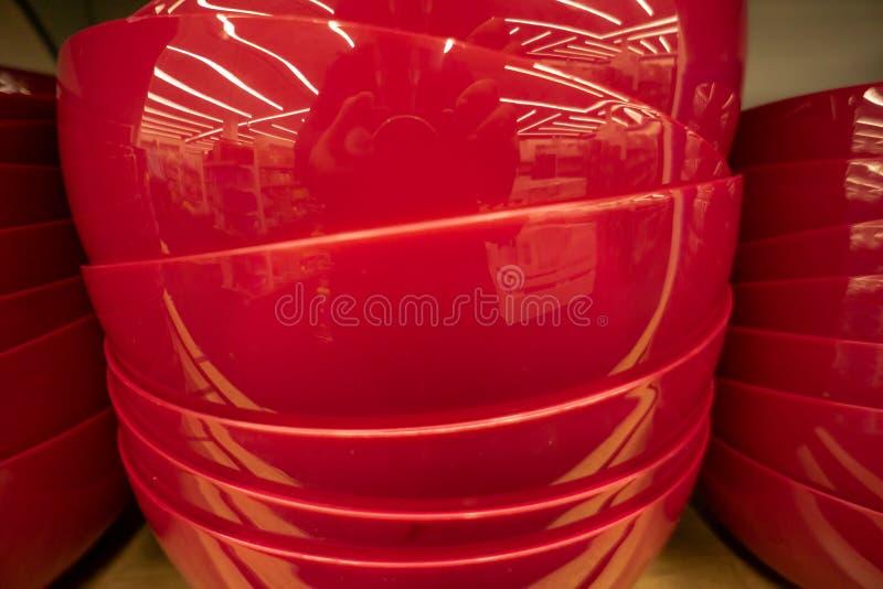 Platos brillantes, placas anaranjadas y blancas y tazas colocándose en el estante blanco Concepto de compra que elige los nuevos  imagen de archivo libre de regalías